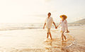 Mature Couple Walking On The Beach At Sunset Royalty Free Stock Photos - 63858778