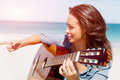 Beautiful Young Woman Playing Guitar On Beach Stock Photos - 63861853