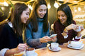 Three Young Beautiful Women Using Mobile Phone At Cafe Shop. Stock Image - 63867761