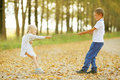 Boy Playing With A Girl In  Autumn Country Road Royalty Free Stock Photography - 63872287