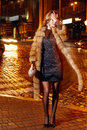 Beautiful Young Sexy Blonde Wearing Evening Makeup In Elegant Fitting Dress Fashionable Stylish Expensive Fur Coat Walk Night Stre Stock Photography - 63976392
