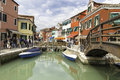 Tourists Walking In Burano City Streets And Boats In The Lagoon In Beautiful City Of Burano Stock Photography - 64006172
