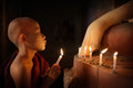 Buddhist Novices Praying With Candlelight In Temple Stock Photo - 64401250