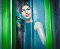 Beautiful Sexy Woman Posing In A Green Painted Window Frame, Shot Through Window. Sexy Gorgeous Young Female With Long Curly Hair Royalty Free Stock Photo - 64475285