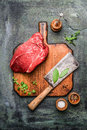Piece Of Fresh Beef Meat On Chopping Board With Meat Cleaver Large And Seasoning On Rustic Background Stock Images - 64483904