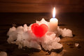 Red Ice Heart And The Burning Candle On A Hill Of White Snow Stock Images - 64493714