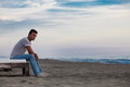 Solitude. Lonely Man On The Beach To The Sea. Stock Image - 64501011