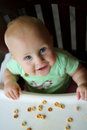 Happy Baby Girl In High Chair Eating Cereal Stock Photos - 64540623