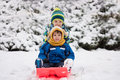 Two Kids, Boy Brothers, Sliding With Bob In The Snow, Wintertime Stock Photos - 64712683