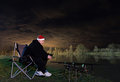 Fisherman In Starry Night With Santa Hat Looking On Rods, Patience Royalty Free Stock Photography - 64773417