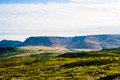 Green Hills With Forest Against Plateau Under Cloudy Sky Stock Images - 64830244