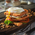 Sandwich With Poached Egg, Tomato, Bacon And Green Salad Royalty Free Stock Photo - 64868485