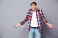 Confused Cute Young Man Standing And Shrugging Royalty Free Stock Photography - 64870347