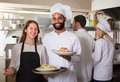 Waitress And Crew Of Professional Cooks Posing At Restaurant Stock Images - 64968324