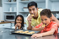 Smiling Father With His Children Eating Biscuits Stock Image - 64969361