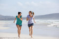 Two Active Women Running And Enjoying Life At The Beach Stock Photography - 65020212