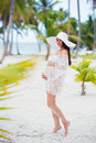 Beautiful Pregnant Girl In White Dress And Wide-brimmed Hat On Beach Near Palm Trees Stock Photography - 65044652