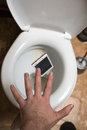 A Man Throws Phone In Toilet Stock Photography - 65146012