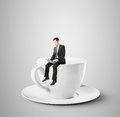 Businessman Sitting On Coffee Cup Stock Photos - 65187053