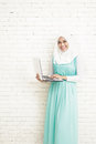 Asian Young Woman Wearing Hijab Standing While Holding A Laptop Stock Photos - 65272113