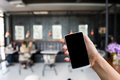 Hand Hold Smart Phone,mobile Over Blurred Image Of Coffee Shop Stock Photo - 65358600