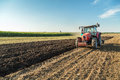 Farmer Plowing Stubble Field With Red Tractor. Stock Images - 65372514