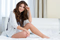 Smiling Positive Carefree Young Woman Sitting On White Bed Stock Photo - 65407360