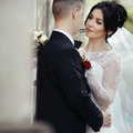 Happy Newlywed Brunette Bride Hugging Handsome Groom Near Old Wa Stock Images - 65468134