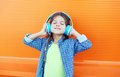 Happy Smiling Child Enjoys Listens To Music In Headphones Over Colorful Orange Royalty Free Stock Photography - 65574717