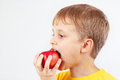 Little Boy In A Yellow Shirt Eating Red Apple Stock Image - 65575021