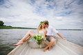 Happy Young Couple Hug Sitting In A Boat On The Lake And Sky Background Royalty Free Stock Images - 65593659