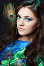 Close Up Beauty Portrait Of Beautiful Girl With Peacock Feather. Creative Makeup Peafowl Feathers. Attractive Mysterious Stock Photo - 65595940
