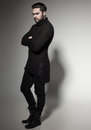 Sexy Fashion Man Model In Black Sweater, Jeans And Boots Posing Dramatic Royalty Free Stock Photo - 65603865