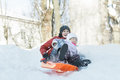 Siblings Having Downhill Fun On Winter Plastic Snow Slider Outdoors Royalty Free Stock Photos - 65645938