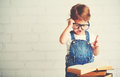 Child Little Girl With Glasses Reading A Books Stock Images - 65686394