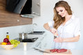 Happy Beautiful Young Woman Cooking Meat On The Kitchen Royalty Free Stock Photos - 65757038