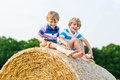 Two Little Children And Friends With Hay Stack Or Bale Stock Image - 65765401