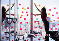 Busy Person Attaching Many Sticky Notes On Large Window Stock Photography - 65797812