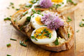 Sandwich With  Adition Of Mackerel Fish , Eggs And Edible Flowers Of Chives On Wooden Table Royalty Free Stock Images - 65909609