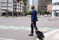 Business Man Walking With Pull Bag In The City Royalty Free Stock Image - 65928426