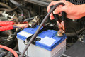 Car Mechanic Uses Battery Jumper Cables Charge A Dead Battery. Stock Photos - 65947593