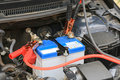 Car Mechanic Uses Battery Jumper Cables Charge A Dead Battery. Stock Photography - 65947672