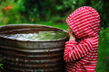 Child Girl In Red Raincoat Playing With Water Barrel In Rainy Summer Garden. Water Economy And Nature Care Stock Photography - 65956772
