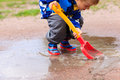 Child Playing In Water Puddle, Kids Spring Activities Stock Photo - 66019950
