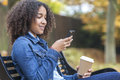 African American Teenager Woman Drinking Coffee And Texting Royalty Free Stock Photography - 66128647