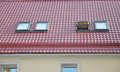 Red Metal Tiled Roof With New Dormers, Roof Windows, Skylights, Rain Gutter System And Roof Protection From Snow Board Royalty Free Stock Photography - 66186367