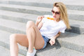 Beautiful Young Cheerful Happy Girl Eating Ice Cream , Smiling In Shorts And A White T-shirt On The Area On A Bright Sunny Day Royalty Free Stock Photography - 66239237