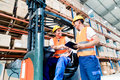 Workers In Logistics Warehouse At Forklift Checking List Stock Photo - 66242150