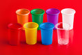 Colored Plastic Glasses On Red Background Stock Photo - 66292620