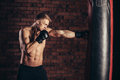 A Young Boxer In Black Gloves With A Naked Torso Work Out Strikes On Punching Bag. Royalty Free Stock Image - 66349556
